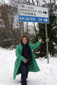 Zane Buzby standing at the sign with the name of her Grandparent's Town